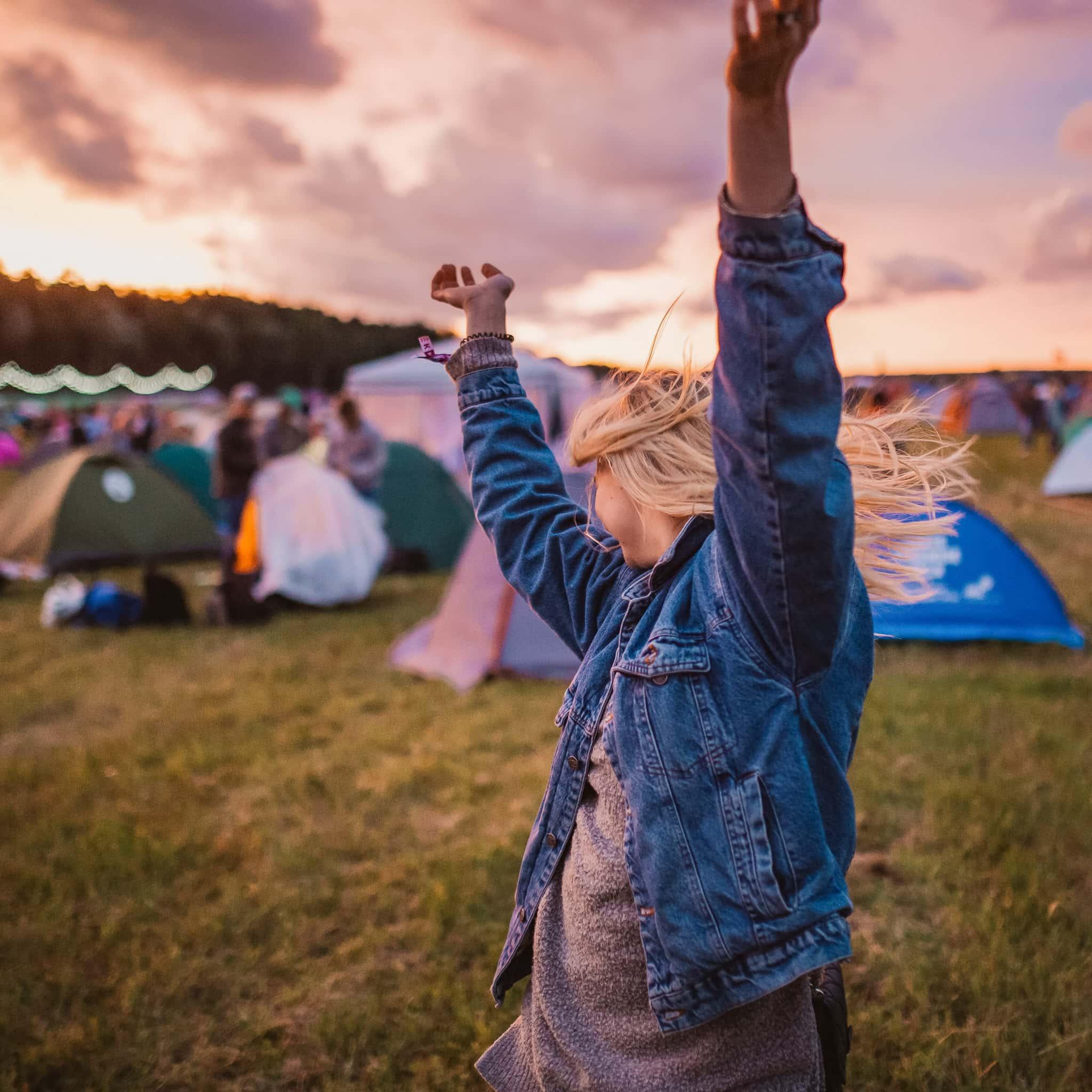 Femme dansant au camping d'un festival